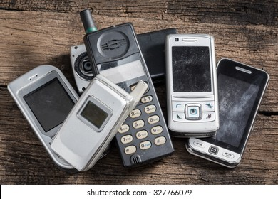 Old and obsolete mobile phone on old wood