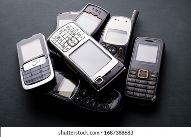 Old and obsoleted cellphones on a black background.
