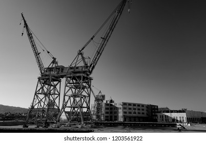 An old ocean port shipping pier with rusting mobile gantry cranes and empty warehouse buildings sits abandoned along a harbor channel.