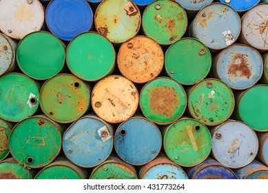 Old oil barrels stacked up in a warehouse, Industrial background.
