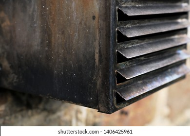 Old oil boiler exhaust flue. Showing the accumulation of soot around the vent cover which if left to block up could cause carbon monoxide build up in the home. Soot shows inefficient burning.