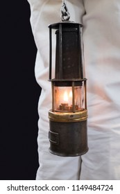 Old oil lamp hold by mining worker with white clothes