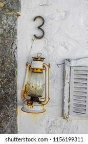 Old oil lantern hanging on a white wall