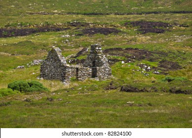 An old one roomed, stone built cottage stands roofless and ruined in the middle of a peat bog in Donegal, Ireland, an abandoned relic acting as a historical reminder of times of poverty or famine.
