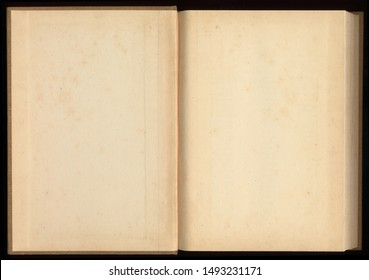 Old open book with blank pages on black background.