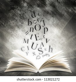 Old open book with magic light and falling letters on a dark abstract background
