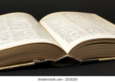 old open book with yellowed pages, black background
