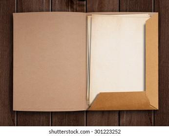 Old open folder on wooden table.