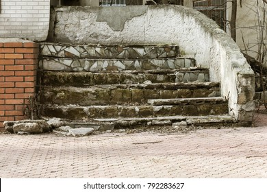 An old open outer stone staircase. Stone, cement steps of the old staircase with traces of weathering and destruction. An ancient stone staircase, ancient broken worn steps. Selective focus