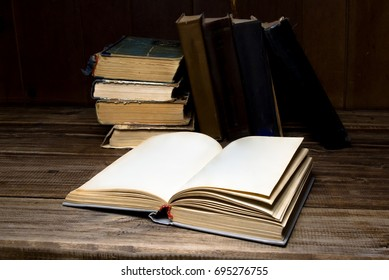 Old opened antique books on a wooden table on the background of a pile books.
