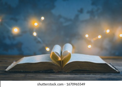 Old opened book, heart shaped paper sheets, dark background with stars and lights, World Book Day, Teachers Knowledge Day, astrology, astronomy and mystery concept, toned vintage