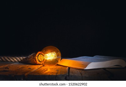 Old opened book and lamp hanging above isolated on black background