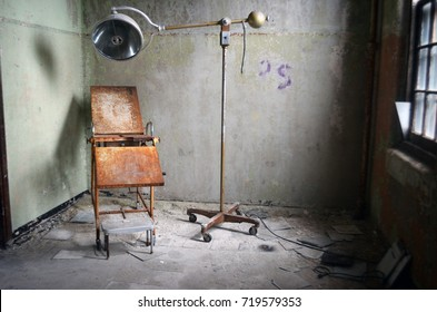 Old operating room with rusty exam operating table in abandoned mental asylum hospital ward building