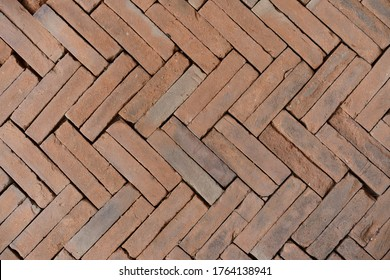 Old orange bricks floor with zigzag pattern texture background.