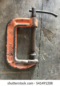 old orange c clamp on wood plate