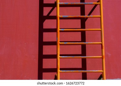Old orange ladder with shadow on red wall