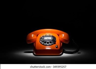 old orange retro phone on black background