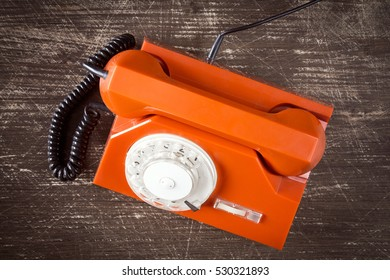 Old orange retro phone with rotary dial. Top view on wooden background.