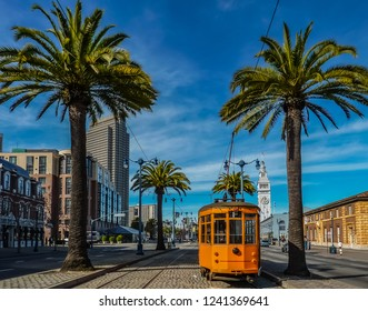 An old orange San Francisco cable car on the Embrcadero with the Ferry Building and palm trees in the background.