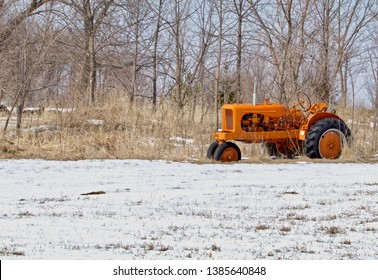 An old orange tractor sits in a snowy field.