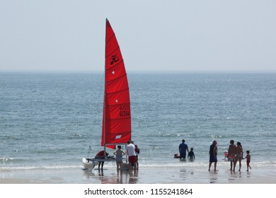 Old Orchard Beach, ME – August 8, 2018: A catamaran with red sails is being set up for an afternoon sail. Sunlight is reflected off the ocean. A few people are nearby down at the water's edge.