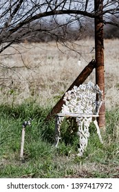 Old ornate metal chair next to water spigot
