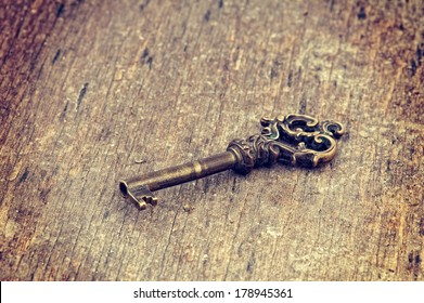Old ornate skeleton key on rough wood background with retro filter effect