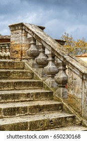 Old ornate stone stair with dark rain clouds