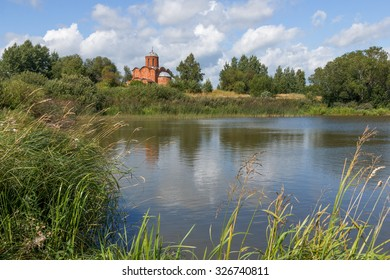 Old orthodox church on the bank of a pond on a summer day. Church of the Savior on Kovalev on the outskirts of Veliky Novgorod