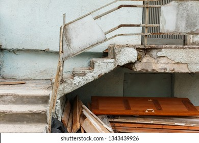 old outdoor staircase in disrepair with peeling paint and pieces of concrete and wooden debris beneath it. destruction of old buildings. side view, daytime.