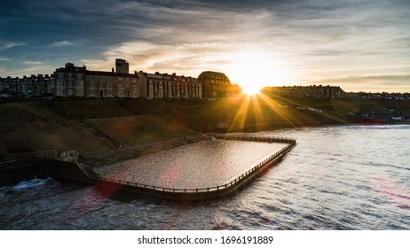 Old outdoor swimming pool at Tynemouth Longsands Beach. Unused, flooded with the tide. Sunset.