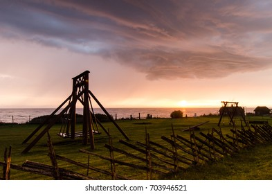 An old overflow swing in an open-air museum during a thunderstorm and sunset at Viimsi, Estonia. The overflow swing is part of the traditional summer celebrations