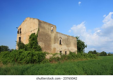 an old overgrown farmhouse in italy set against a blue sky