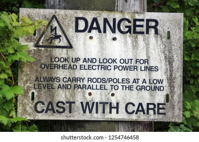Old overhead electric cable warning sign for anglers at a scottish loch