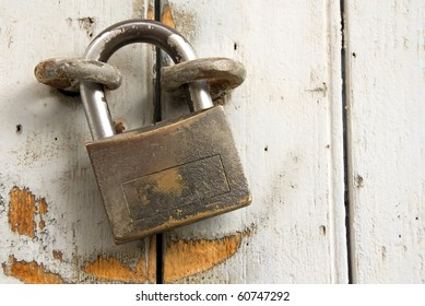 Old Padlock closing a white wooden door