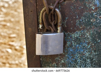 old padlock hanging on a rusty chain and a metal gate