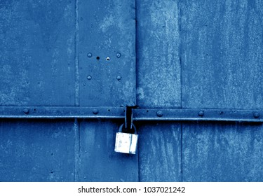 Old padlock on metal gate in navy blue tone. Abstract background and texture.