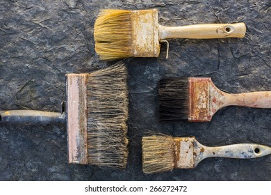 Old paint brushes on a stone surface