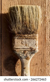 Old paint brushes on a wooden surface