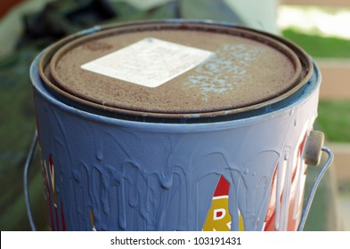 Old Paint Can with Dried Blue Paint Dripping down Side