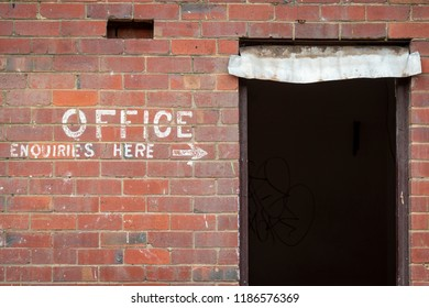 Old painted sign, Office Enquiries Here, on a red brick wall and an open doorway