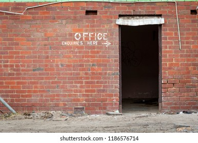 Old painted sign, Office Enquiries Here, on a red brick wall and an open doorway in a demolition site