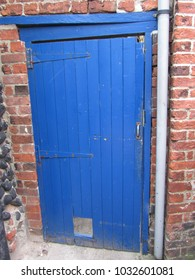 Old painted wooden door showing age and interest and weathering.cottage UK
