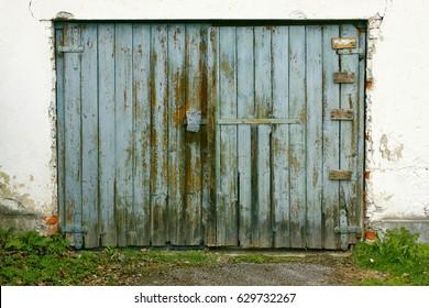 Old painted wooden garage door of blue color