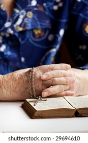 An old pair of hands with a book and cross - shallow depth of field with focus on cross