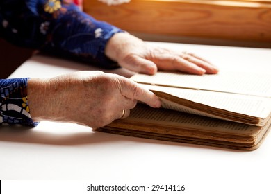 An old pair of hands holding the pages in a book, reading.