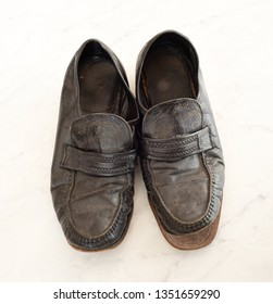 Old pair of Mens black dress shoes that are worn out, very dusty and dirty and falling apart.  They need polish and repair