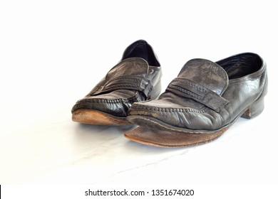 Old pair of Mens leather black dress shoes that are worn out, very dusty and dirty and falling apart.  They need polish and repair