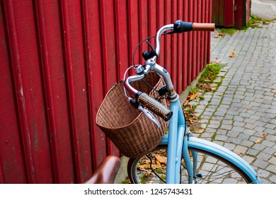 An old pale blue bike with a brown braided basket. The bicycle parked outside a red wooden building in a small cobblestone street. Closeup view, retro / vintage style.
