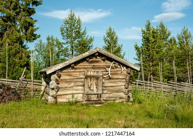 Old and pale farm cabin made of timber at an old abandoned hill farm in northern Sweden. On a beautiful summer day with sunshine and blue sky